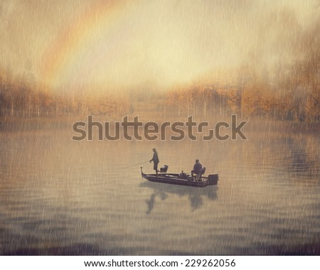 Retro style landscape image man and old guy fishing in a boat on a rainy foggy day with rainbow and fall autumn forest background. Peaceful nature leisure vacation hobby activity lifestyle concept - stock photo