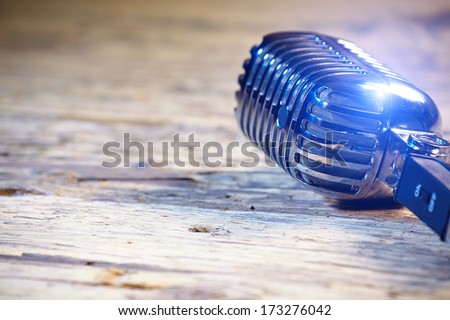 Retro style microphone on old wood table  or stage - stock photo