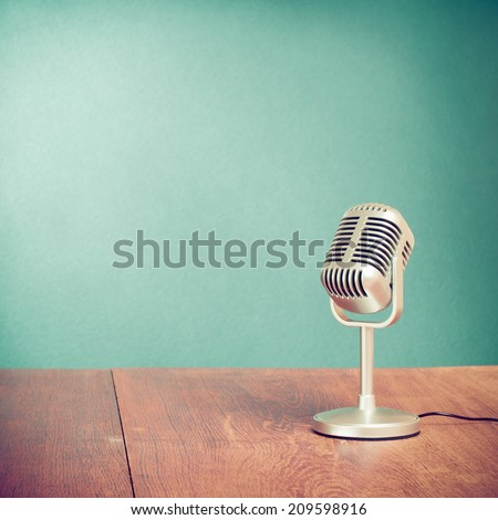 Retro style microphone on table front aquamarine wall background - stock photo