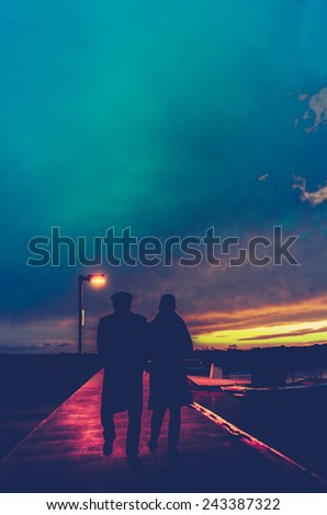 Retro Style Photo Of A Romantic Couple Under A Streetlight At A Marina At Sunset With Copy Space - stock photo