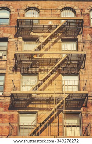 Retro style photo of New York building with fire escape ladders, USA. - stock photo