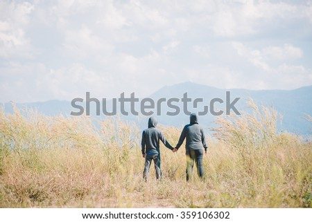 retro style picture of two people standing and holding hands in the prairie during winter.