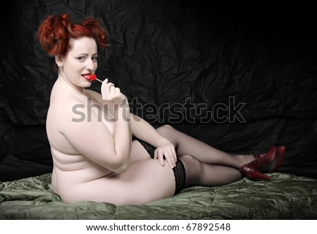 Retro style picture overweight woman with red lollipop. Low key studio shot with black background. - stock photo