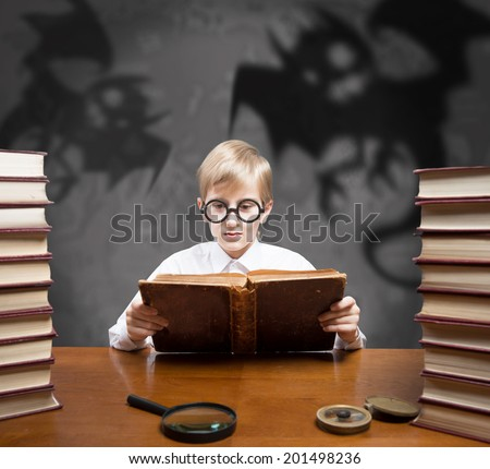 Retro style portrait of a boy reading the old book of spooky stories