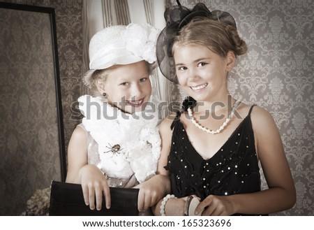 Retro style portrait of little girls try on a Grandma's dress  - stock photo