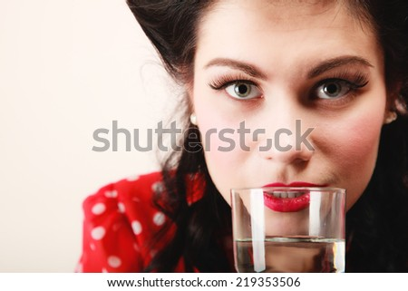 Retro style. Portrait of stylish young woman brunette pinup girl drinking water drink beverage from glass  - stock photo