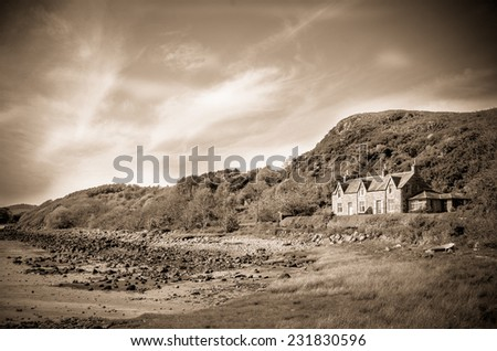 Retro Style Sepia Photo Of A House By Sea In The Countryside - stock photo
