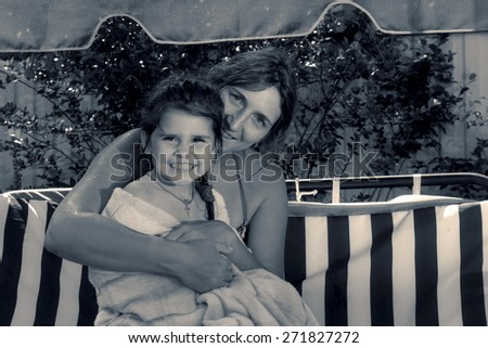 Retro style special toned photo of little girl and her mother in the summer garden hugging on a swing - stock photo