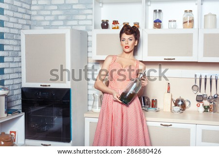 Retro style. The woman in the kitchen in the hands holding a bottle of soda. - stock photo