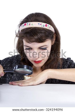 Retro style woman looking for something with a magnifying glass for composites.  She is looking at a blank surface. - stock photo