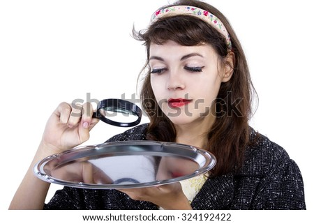 Retro style woman looking for something with a magnifying glass on a tray.  The tray is empty for composites. - stock photo