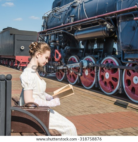 retro style. Woman traveler sitting on wooden bench on platform of Railway Station. Near old train . Cute lady wait train and read the vintage book Girl wear long white dress Leather case stand near  - stock photo
