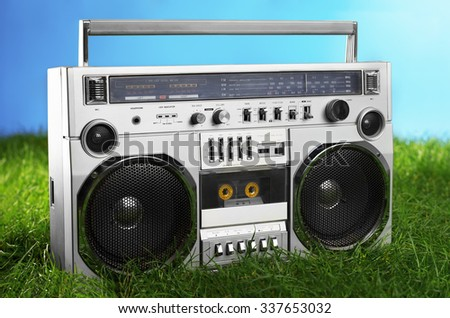 Retro styled boom box blaster on fresh green grass, blue background - stock photo