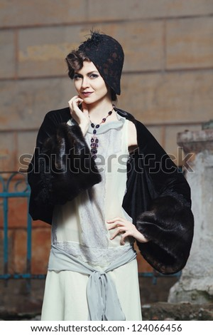 Retro styled fashion portrait of a handsome. Clothing and make-up in 1920's style. - stock photo