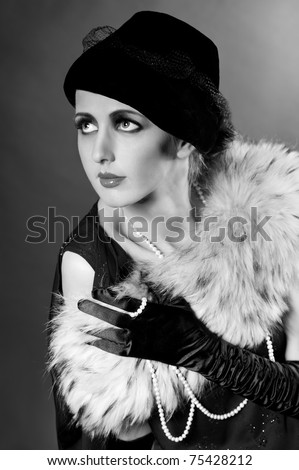 Retro styled fashion portrait of a young woman with pearls. Clothing and make-up in vintage style - stock photo