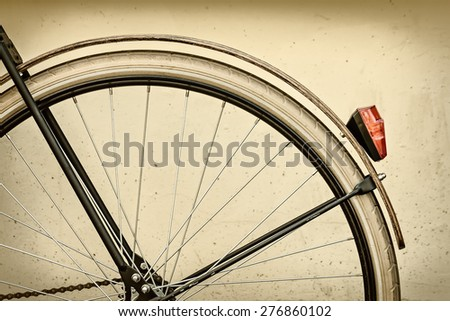 Retro styled image of a bicycle rear wheel with wooden fender - stock photo