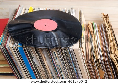 Retro styled image of a collection of old vinyl record lp's with sleeves on a wooden background. Browsing through vinyl records collection. Music background. - stock photo