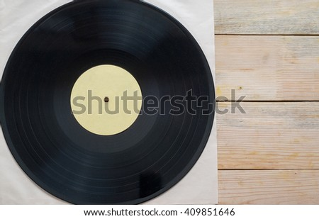 Retro styled image of a collection of old vinyl record lp's with sleeves on a wooden background. Copy space. Top view - stock photo