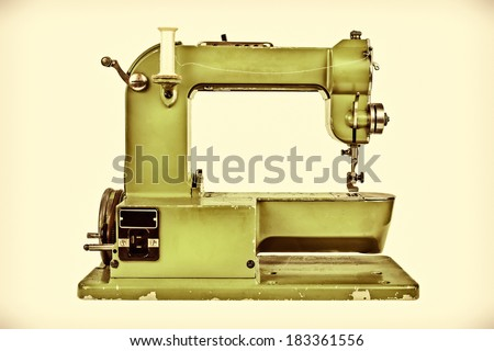 Retro styled image of an old sewing machine against a light sepia background - stock photo