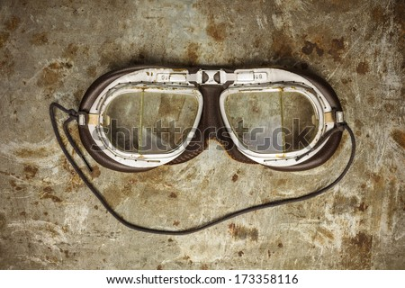 Retro styled image of old leather race goggles on a rusty steel background - stock photo