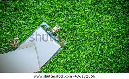 Retro styled or retro color name tag or identification holder with metal clip on fake grass. Concept of garden wedding event or invitation. Slightly de-focused and close-up shot. Copy spac