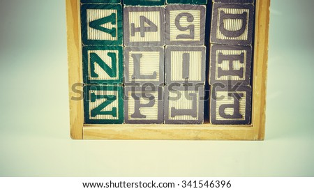 Retro styled or retro color stack or scattered alphabet wooden block letters and numbers. Concept of old education. Slightly de-focused and close-up shot. Copy space. - stock photo