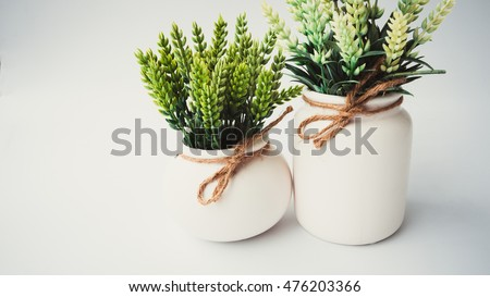 Retro styled or retro color synthetic barley grass or lavender plant in a white pot. Concept of minimalist decoration. Slightly de-focused and close-up shot. Copy space.