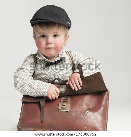 Retro styled toddler with old school bag - stock photo