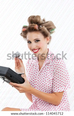 Retro styled woman holding tape recorder and cassette - stock photo