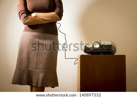 Retro styled woman operating a slide projector with a wired remote control - stock photo