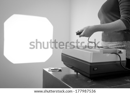 Retro styled woman operating a slide projector with a wired remote control in black and white
