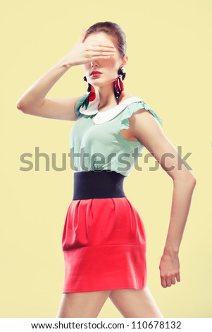 Retro styled young woman covers her eyes with one hand. She's wearing big fancy earrings and red mini, yellow background - stock photo