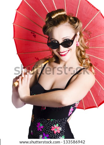 Retro styled young woman with old-fashioned hairstyle holds a red paper sunshade - stock photo