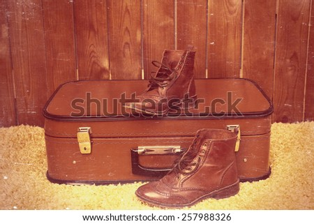 Retro suitcase with male shoes on fur carpet on wooden background