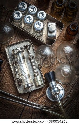 Retro syringe, stethoscope and medical cupping glass on a wooden table. - stock photo