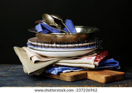Retro tableware and napkins on old wooden table, on dark background - stock photo