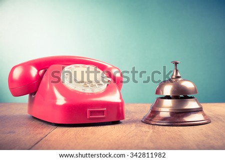Retro telephone and hotel reception service desk bell. Old style filtered photo - stock photo