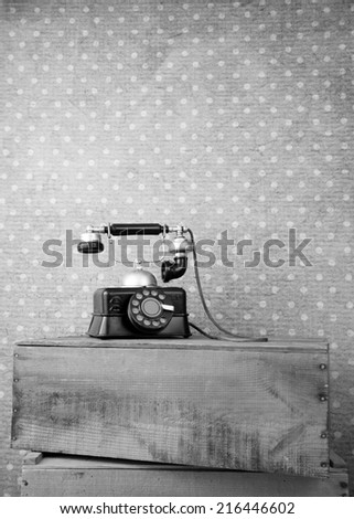 Retro telephone on a box in front old wallpaper in black and white - stock photo