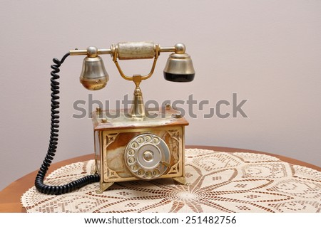 Retro telephone on the brown table with handmade table cloth. Vintage style photo - stock photo