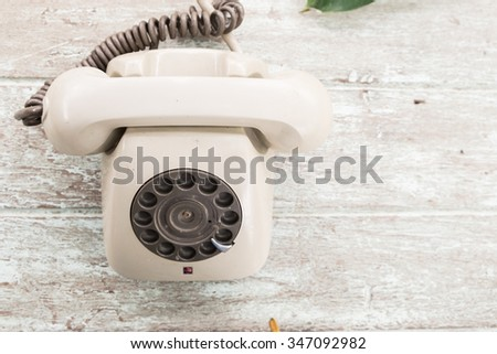 Retro telephone on wood table, top view - stock photo