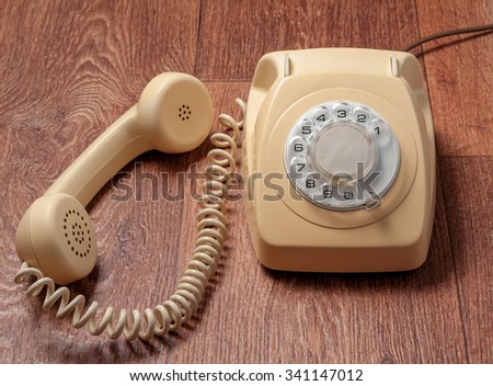 Retro telephone on wooden table in front gradient background.