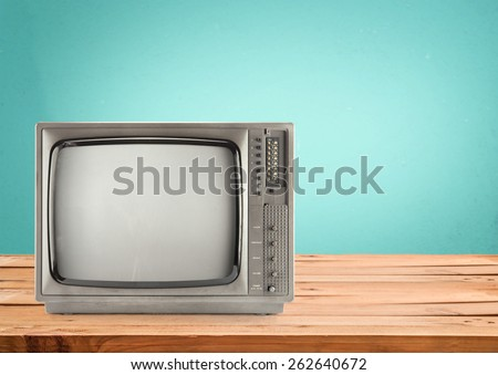 Retro Television on wood table with vintage aquamarine wall background - stock photo