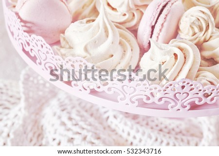 Retro toned homemade pink and white meringues on a plate.