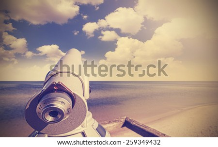 Retro toned picture of telescope on a beach pointed at beautiful sky. - stock photo