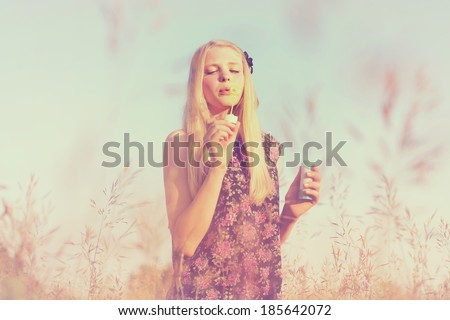 Retro toned portrait of slim young girl making soap bubbles in summer field - stock photo