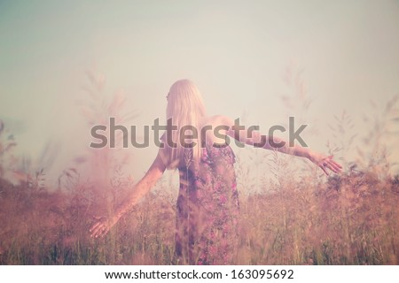 Retro toned portrait of young girl in summer field from back - stock photo