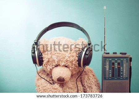 Retro toy Teddy Bear with headphones and radio receiver front mint green background - stock photo