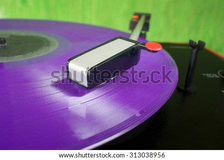 Retro turntable with purple vinyl record, close up, selective focus - stock photo