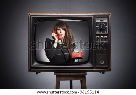Retro TV on the screen says the young woman in a retro phone. - stock photo