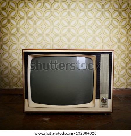 retro tv with wooden case in room with vintage wallpaper and parquet - stock photo